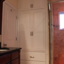 Custom built-in linen cabinet for a client that needed extra storage in the master bathroom. I built and installed a custom 42″ wide by 16″ deep by 108″ tall cabinet behind the door in an otherwise unused space. The cabinet features 2 deep full extension drawers, raised panel doors with applied molding, and fluted casing with rosettes to match the existing style of vanity cabinetry.