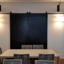Custom barn doors and paneling in a restaurant private dining room to conceal the recessed television cabinet.