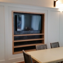 Custom white oak television display cabinet before installation of custom barn doors.